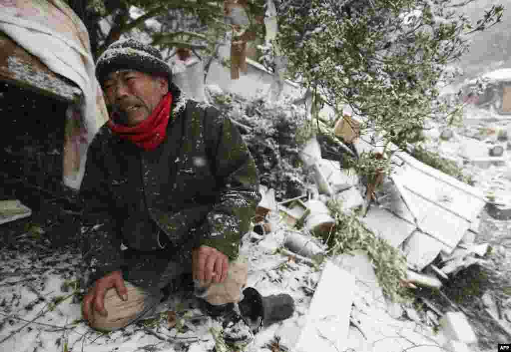 Город Онагава. Пострадавший оплакивает членов своей семьи, погребенных под завалами его дома. 17 марта 2011 год