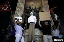 "Supporters of Turkish President Tayyip Erdogan hold an effigy of U.S.-based cleric Fethullah Gulen hanged by a noose on the Republic Monument, during a pro-government demonstration on Taksim Square in Istanbul, Turkey, July 18, 2016. The placards read ""Ex"