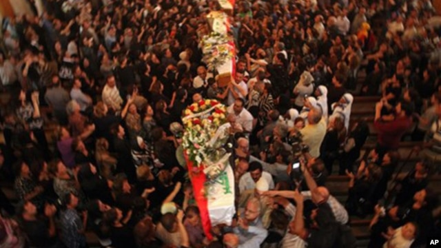 Mourners carry the coffins of slain Christians during their funeral in Baghdad, Iraq, Tuesday, Nov. 2, 2010. The victims were killed Sunday when gunmen stormed a church during mass and took the entire congregation hostage.