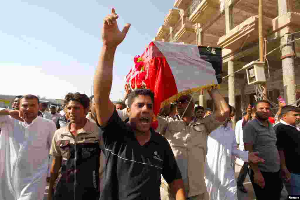 Mourners carry the coffin of a Shi'ite volunteer who joined the Iraqi army and was killed during clashes with the Islamic State of Iraq and the Levant, Najaf, Iraq, June 28, 2014.