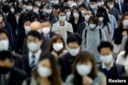 People wear face masks at Shinagawa station during the rush hour after the government expanded a state of emergency to include the entire country following the coronavirus disease (COVID-19) outbreak, in Tokyo, Japan, April 20, 2020.