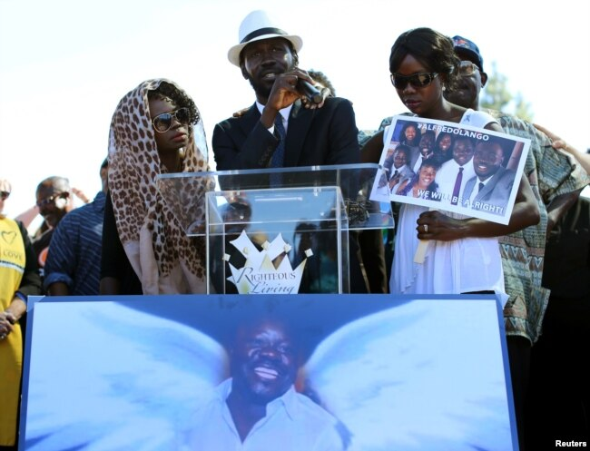FILE - Apollo Olango, center, brother of Alfred Olango, speaks to a crowd of supporters as demonstrators hold a rally to protest the fatal police shooting of Ugandan immigrant Alfred Olango in El Cajon, California, Oct. 1, 2016.