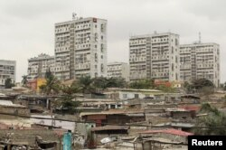 FILE - High-rise buildings are seen behind informal settlements in the capital of Luanda, Angola, Aug. 30, 2012.