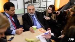 叙利亚新闻部长左比(左二)在日内瓦和平会谈间歇回答记者问题。(2014年1月28日)