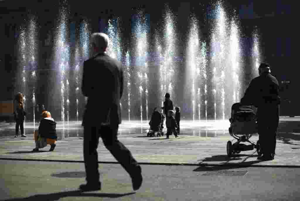 Personas ven una fuente de agua en la plaza Federal de Berna en Suiza. Hoy se celebra el Día Mundial del Agua que tiene el objetivo de debatir la seguridad alimentaria y el acceso a este elemento.