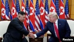 Prezidan Trump (adwat) ki t ap bay Kim Jong Un lanmen pandan yon rankont nan zòn demilitarize a ant 2 Kore yo.