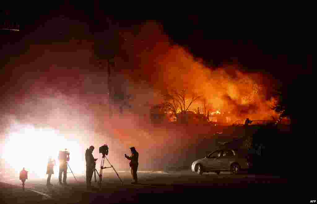 Media members report on a burning home as a firefighter douses flames (R) during the Hillside Fire in the North Park neighborhood of San Bernardino, California.