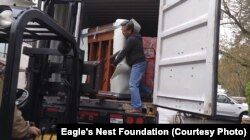 Workers from Eagle's Nest Foundation load pianos donated by Dean Petrich onto a truck to begin their trip to Cambodia.