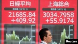 一名男子2019年7月1日走過東京一處股票交易所外顯示日經指數和上證綜指的電子屏幕。