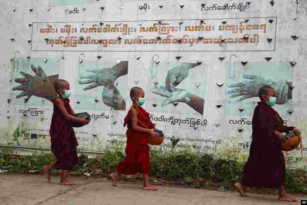Buddhist novice monks wearing face masks walk past a COVID-19 awareness sign as they collect morning alms, in Yangon, Myanmar.