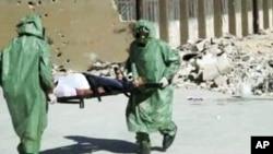 Những người trong trang phục bảo hộ và mặt nạ chống độc tiến hành diễn tập điều trị thương vong của một cuộc tấn công vũ khí hóa học ở Aleppo, Syria.