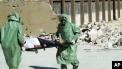 FILE - People in protective suits and gas masks conduct a drill on how to treat casualties of a chemical weapons attack in Aleppo, Syria. Islamic State fighters reportedly fired rockets loaded with mustard gas into a town north of Baghdad late Tuesday and early Wednesday.