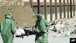 FILE - People in protective suits and gas masks conducting a drill on how to treat casualties of a chemical weapons attack in Aleppo, Syria.