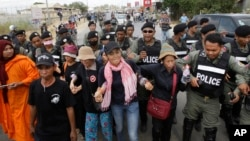 Cambodian civil rights supporters are forcibly directed by riot police as they march in protest of charges brought against local rights activists near Prey Sar prison, outside Phnom Penh, Cambodia, May 9, 2016.