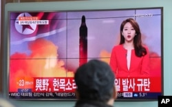 "FILE - A man watches a TV news program reporting about North Korea's missile launch in Seoul, South Korea, Feb. 12, 2017. The letters read ""The ruling and the opposition parties denounce North Korea's missile launch."""