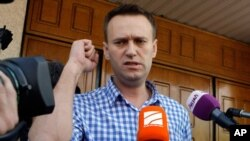 Russian opposition leader Alexei Navalny speaks to the media at the headquarters of the Russian Investigation committee in Moscow, Russia, June 12, 2012.