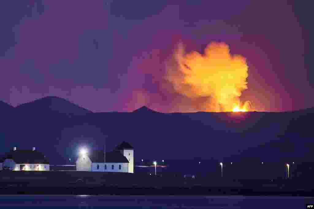 Bessastadir, the official residence of the President of Iceland is seen with the glow from the lava coming out of a fissure near the Fagradalsfjall on the Reykjanes Peninsula behind.