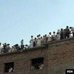 Znatiželjni mještani Abbottabada sa krova obližnje zgrade promatraju kompleks zgrada u kojima je živio Osama bin Laden