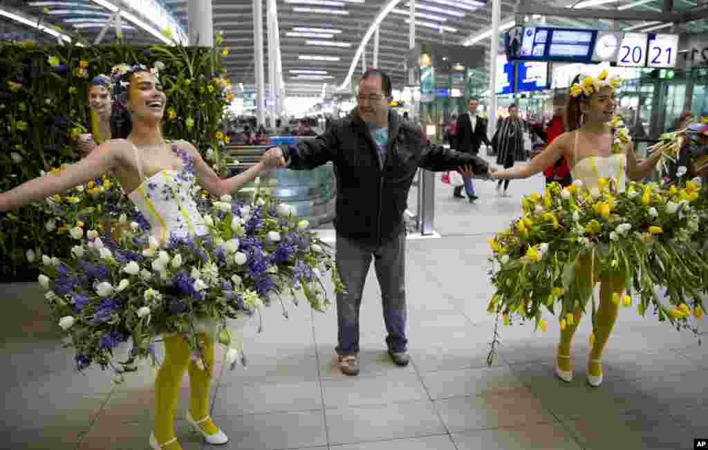 Models in Utrecht, Netherlands, wear floral arrangements as they interact with travelers to promote Keukenhof, the largest flower show in the world.