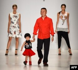 Designer Zhuliang Li (C) appears on the runway with model Danielle Knudson (L) and Miss Teen USA K. Lee Graham (R) at the Oudifu fashion show during Mercedes-Benz Fashion Week Spring 2015.