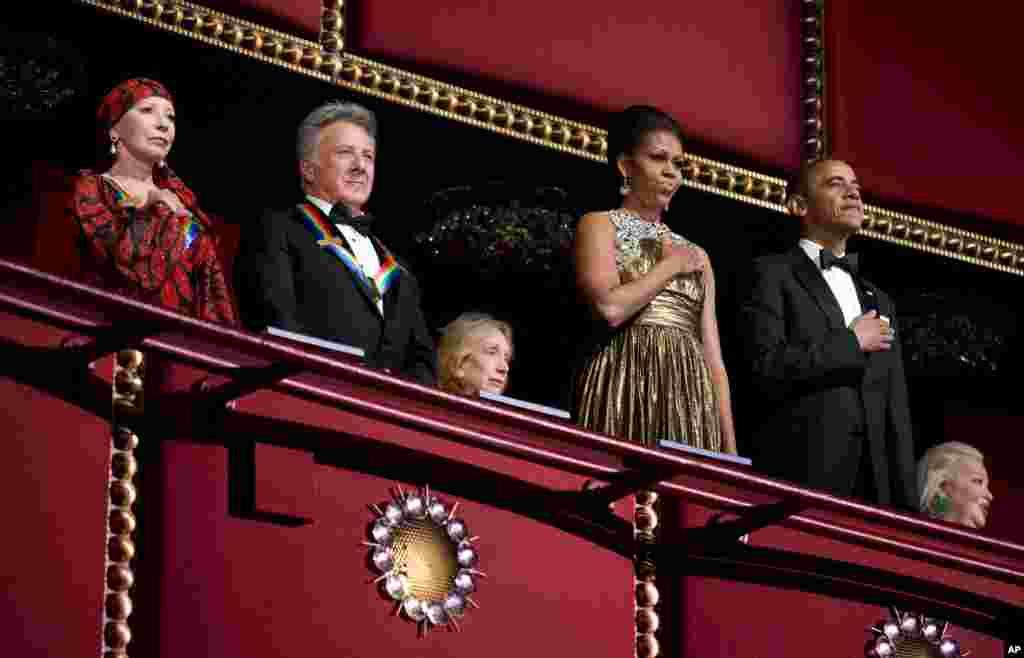 El presidente Barack Obama y su esposa Michelle entonan el himno de EE.UU. durante la ceremonia de la entrega de premios a las artes del Kennedy Center. Acompañan a la pareja presidencial el actor Dustin Hoffman y la bailarina Natalia Makarova.