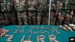 Binh sĩ Ấn Độ bên cạnh các vũ khí và đạn dược tịch thu được tại một căn cứ quân sự ở Prang, khoảng 45 km (28 dặm) về phía đông bắc Srinagar, Ấn Độ, ngày 30/8/2013.