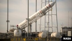 The Orbital Science Corporation Antares rocket is seen as it is raised into position at launch Pad-0A at NASA's Wallops Flight Facility, Wallops Island, Virginia, Dec. 17, 2013.