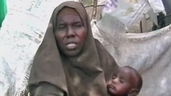 Woman & her child in the Badbaado IDP refugee camp in Mogadishu, Somalia.