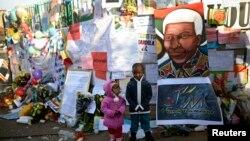 Trẻ em chụp hình bên ngoài Bệnh viện nơi cựu Tổng thống Nam Phi Nelson Mandela đang được điều trị ở Pretoria, Nam Phi, ngày 27/6/2013.