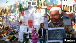 Anak-anak Afrika Selatan berpose di depan rumah sakit jantung Medi-Clinic, tempat mantan Presiden Afrika Selatan Nelson Mandela dirawat di Prestoria, Afrika Selatan (27/6). Kondisi Mandela dikabarkan lembali stabil setelah mengalami masa kritis.