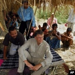 FILE - Microsoft co-founder Bill Gates, center, speaks with a villager in Aulali, Khagaria district, before heading to Guleria, in Bihar state, Wednesday, May 12, 2010.