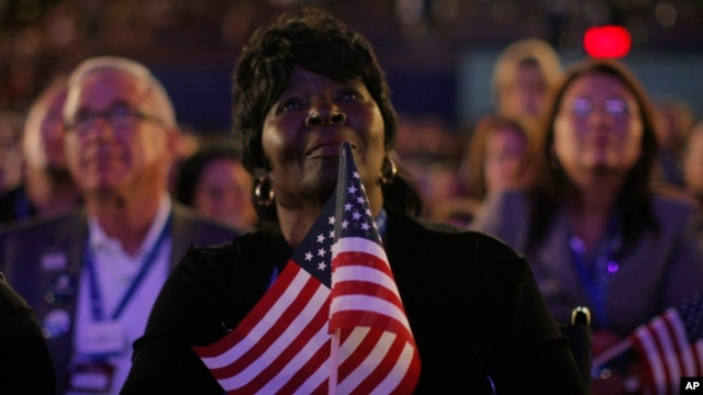 FILE - Superdelegate Margie Woods of Will County, Ill., listens to Michelle Obama, wife of then-Democratic presidential candidate Barack Obama, speak during the Democratic National Convention in Denver, Aug. 25, 2008.