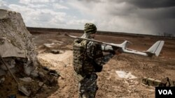 A pro-Kyiv drone operator carries one of the homemade aircraft used to gather intelligence. (Adam Bailes/VOA News)