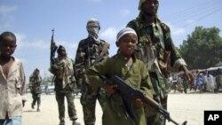 Seorang anak laki-laki bersenjata bersama para pejuang al-Shabab dalam latihan militer di Suqaholaha, Somalia. (Foto: Dok)