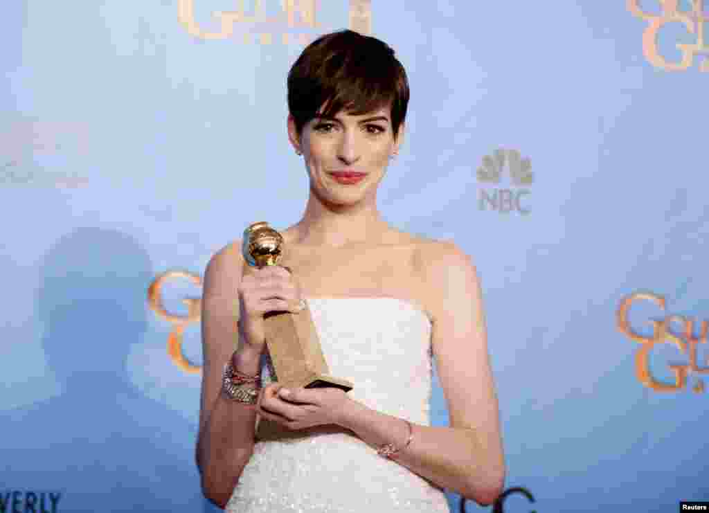 "Anne Hathaway holds the award she won for Best Supporting Actress in a Motion Picture, Comedy or Musical for her work in ""Les Miserables"" backstage at the 70th annual Golden Globe Awards in Beverly Hills, California, January 13, 2013."