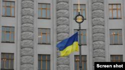 Украинский национальный флаг перед зданием правительства в центре Киева