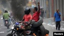 2 neg kap pase sou yon motosiklèt nan yon ri nan Pòtoprens kote kawotchou ap boule. Pòtoprens, Ayiti, 10 jiyè 2019. Foto: REUTERS/Andres Martinez Casares
