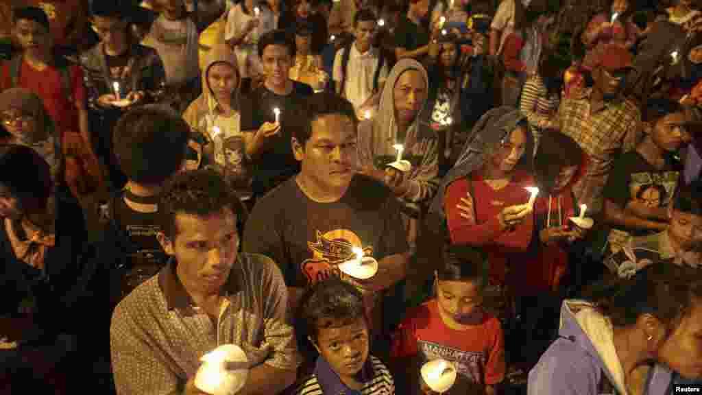 Indonésios fazem vigília pelas vítimas do AirAsia 8501 em Surabaya. O avião da Air Asia caiu a 28 de Dezembro. Indonésia Dez. 31, 2014.