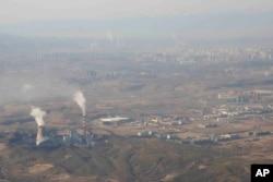 Asap dan uap mengepul dari Pembangkit Listrik Tenaga Panas Urumqi di Urumqi di Daerah Otonomi Uyghur Xinjiang China barat, 21 April 2021. (Foto: AP)