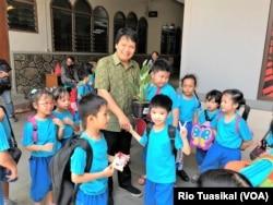 Para murid SD BPK Penabur memberikan tanaman sebagai tanda mata kepada Sonny Hermawan, perwakilan gereja Katolik St. Mikael, Bandung, Jumata, 15 November 2019. (Foto: Rio Tuasikal/VOA)