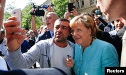 FILE - A migrant takes a selfie with German Chancellor Angela Merkel outside a refugee camp near the Federal Office for Migration and Refugees after registration at Berlin's Spandau district, Germany, Sept. 10, 2015.