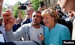 ជនចំណាកស្រុកមួយរូបថតរូប selfie ជាមួយលោកស្រីអធិការបតី Angela Merkel ខាងក្រៅជំរំជនភៀសខ្លួនមួយកន្លែងនៅក្រុងប៊ែរឡាំងកាលពីថ្ងៃទី១០ ខែកញ្ញា ឆ្នាំ២០១៥។