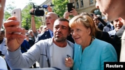 Kanselir Jerman Angela Merkel disambut meriah oleh pengungsi Suriah dan dijuluki 'Mama Merkel' saat berkunjung ke pusat registrasi migran di distrik Spandau, Berlin hari Kamis (10/9).
