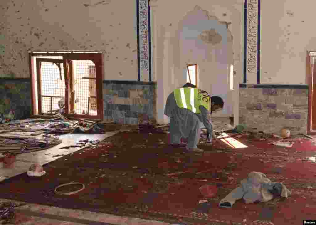 A rescue worker collects evidence after an explosion in a Shi'ite mosque in Shikarpur, located in Sindh province, Pakistan, Jan. 30, 2015.