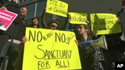 FILE - Protesters in San Francisco hold up signs in support of sanctuary cities, April 14, 2017.