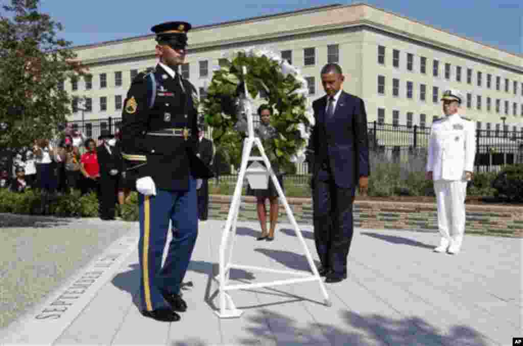 President Barack Obama and first lady Michelle Obama lay a wreath as the 10th anniversary of the September 11 attacks are observed at the Pentagon in Washington, Sunday, Sept. 11, 2011. At right is Chairman of the Joint Chiefs of Staff Adm. Mike Mullen. (