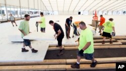 Workers assemble flooring in Temporary structures outside the Wells Fargo Center ahead of the the 2016 Democratic National Convention in Philadelphia, June 22, 2016. (AP Photo/Matt Rourke)