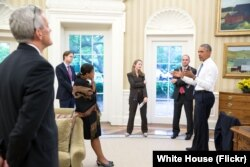 FILE - President Barack Obama talks with national security staff in the Oval Office after being notified of the nuclear agreement with Iran, July 13, 2015.