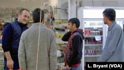 Des migrants afghans discutent avec un employé turc dans un supermarché halal à Reims.
