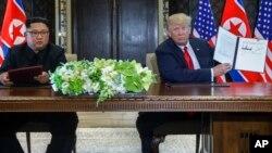 도널드 트럼프 미국 대통령(오른쪽)과 김정은 국무위원장이 12일 싱가포르 카펠라 호텔에서 미북 정상회담 공동성명에 서명했다.